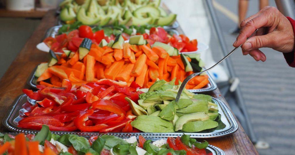 Eine Hand mit Gabel piekt in kleingeschnittene Avocadoscheiben, die zusammen mit Paprika, Mohrrüben und anderer Rohkost auf Platten liegt