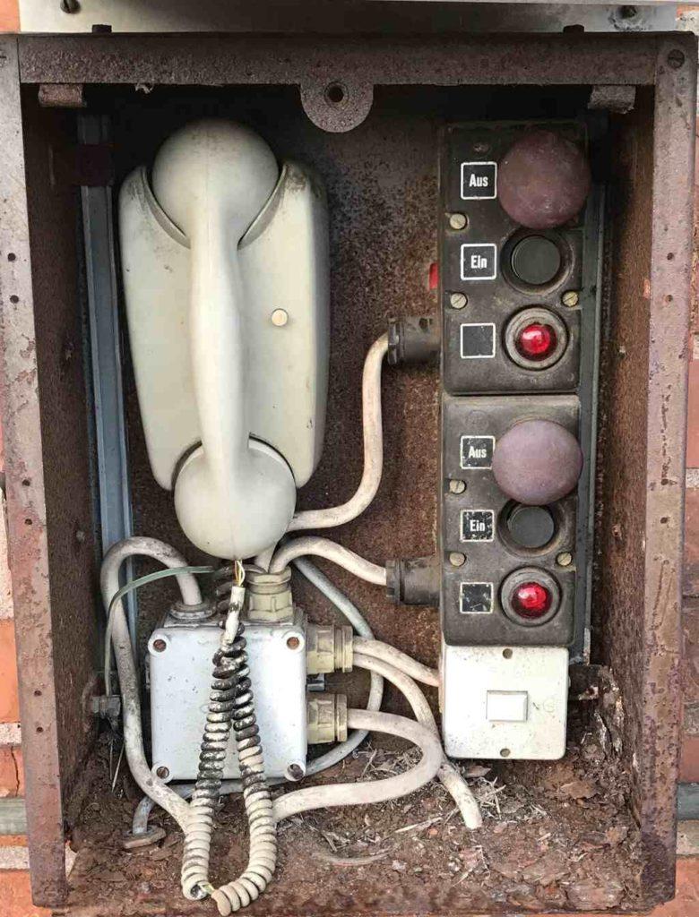 altes Kabeltelefon mit Ein- und Ausschaltknöpfen bei Lagergebäude