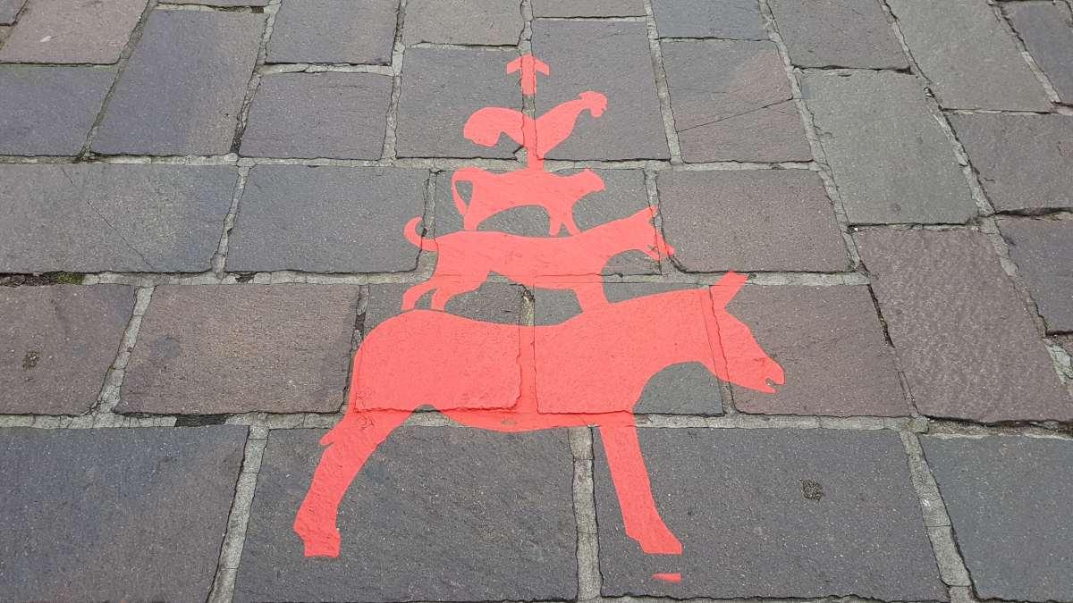 Die Bremer Stadtmusikanten als Wegweiser mit roter Farbe auf Pflastersteine gesprüht