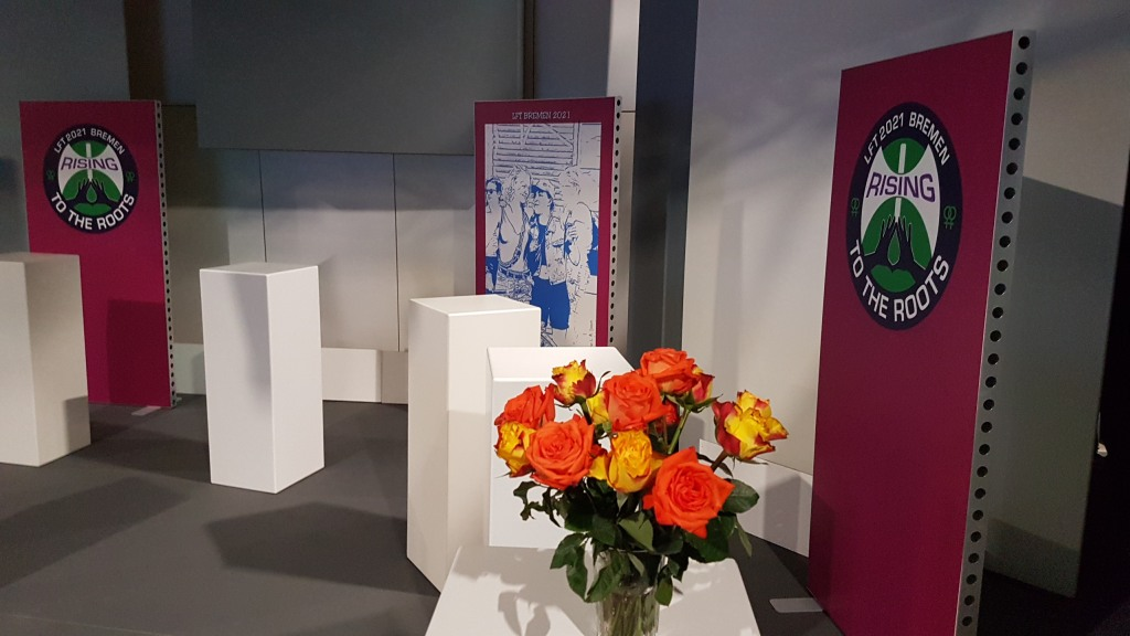 Bild vom Studio mit Stehpulten und Stellwänden mit LFT2021-Logo und Kunstplakat und einem Strauss orange-gelbe Rosen