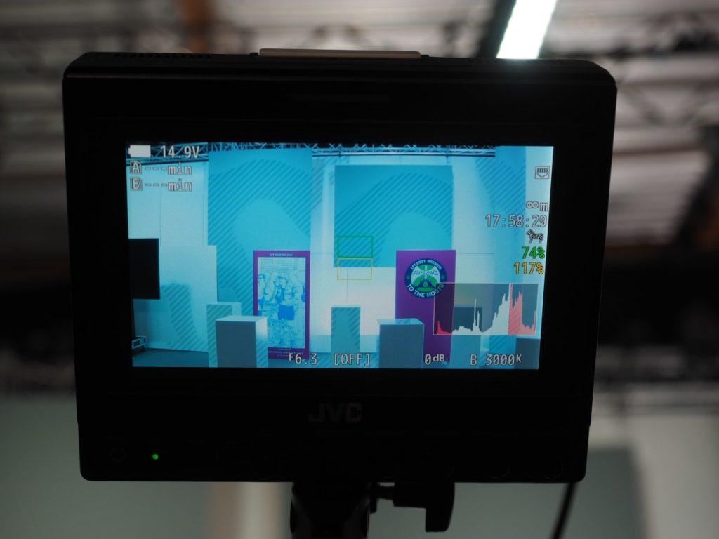 Blick durch das Kamera-Display ins Studio mit dem Kunstplakat und dem Logo vom LFT2021